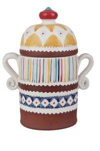 A photo of a handmade ceramic storage jar with intricate decoration