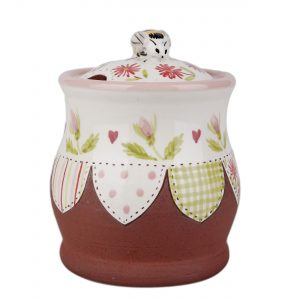 A photo of a handmade ceramic honey pot with decorative bee on top
