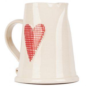 A photo of a handmade ceramic white jug with heart design