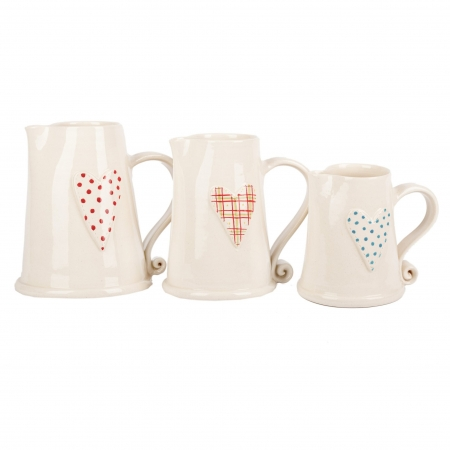 A photo of Three handmade ceramic white jugs with heart design in sizes small, medium and large