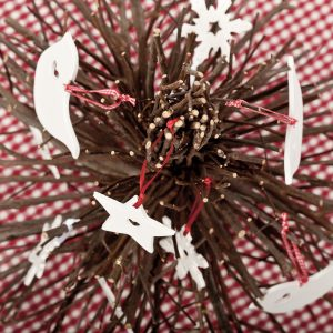 A photo of a selection of white christmas decorations on a wooden tree and checked gingham tablecloth