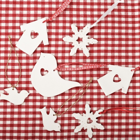 A photo of a selection of white christmas decorations on a checked gingham tablecloth