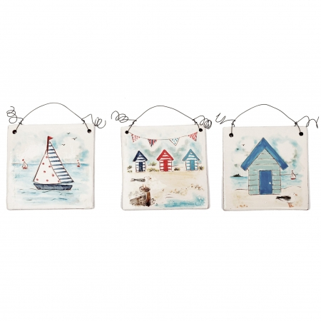 A photo of three handmade ceramic Seaside design decorative tiles