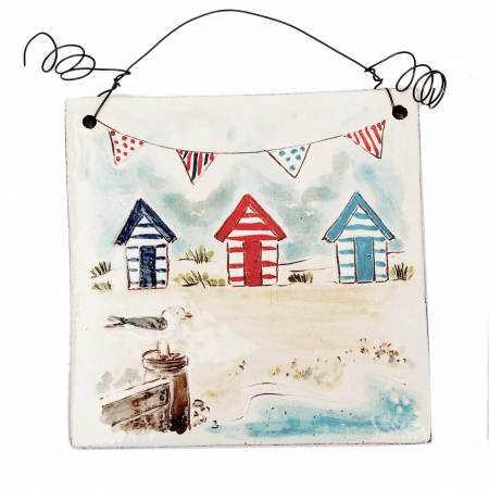 A photo of a handmade ceramic seaside hanging tile