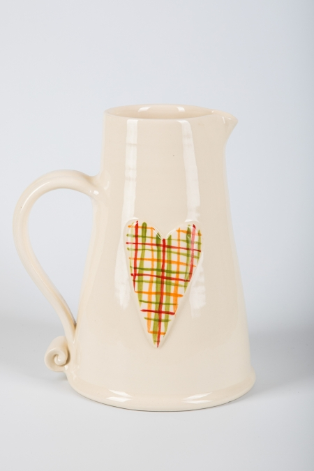 A photo of a White ceramic jug with ceramic decorated heart on the side