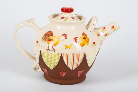 A photo of a decorative ceramic teapot with two-tone/patchwork design with two chickens on the side