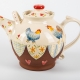 A photo of a decorative ceramic teapot with two-tone/patchwork design with two blue chickens on the side