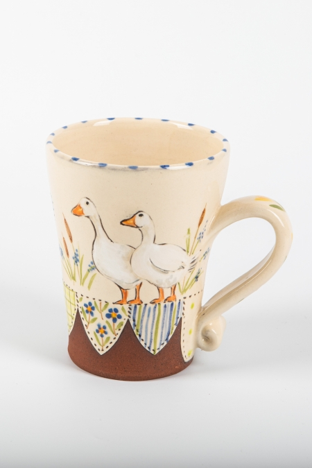 A photo of a decorative ceramic mug with two-tone/patchwork design with two ducks on the side