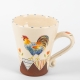 A photo of a decorative ceramic mug with two-tone/patchwork design with a chicken on the side