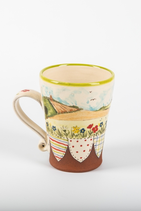 A photo of a decorative ceramic mug with two-tone/patchwork design with landscape scenery on the side