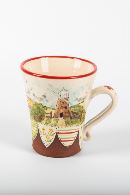 A photo of a decorative ceramic mug with two-tone/patchwork design with landscape scenery and windmill on the side