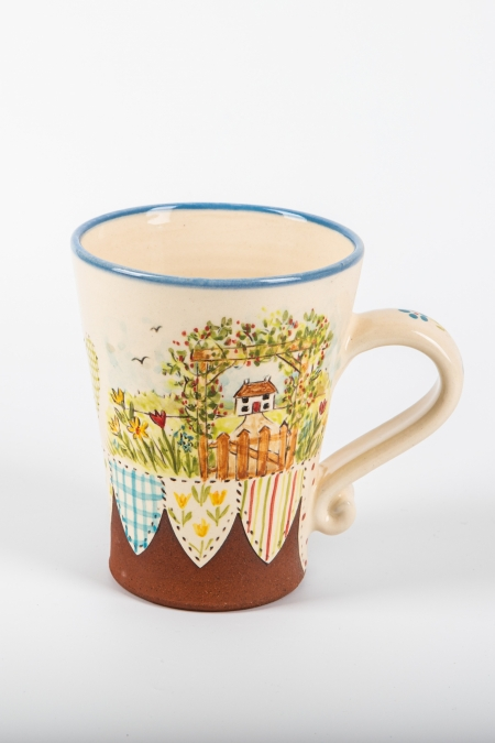 A photo of a decorative ceramic mug with two-tone/patchwork design with a cottage on the side