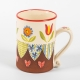 A photo of a decorative ceramic mug with two-tone/patchwork design and flowers on the side