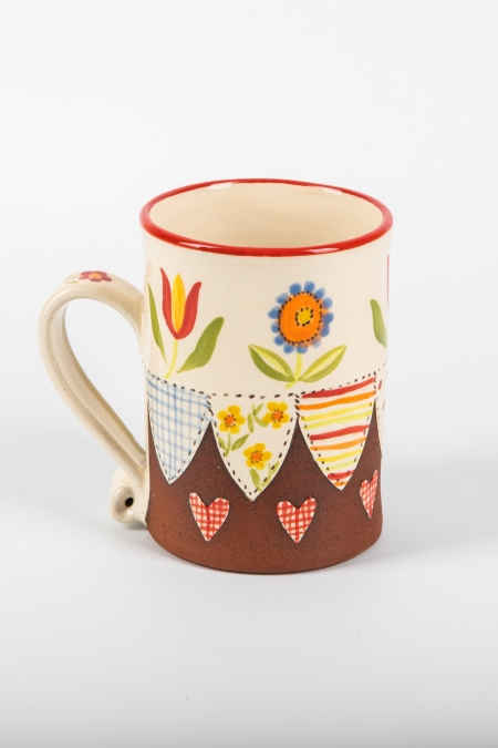 A photo of a decorative ceramic mug with two-tone/patchwork design with flowers on the side