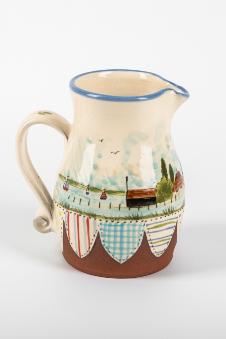 A photo of a decorative ceramic Jug with two-tone/patchwork design with landscape decoration on the side