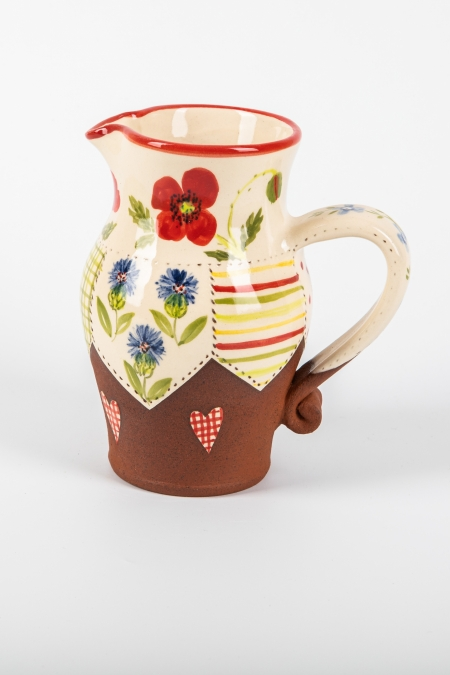 A photo of a decorative ceramic jug with two-tone/patchwork design and red poppy flowers on the side