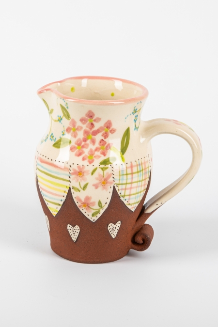 A photo of a decorative ceramic jug with two-tone/patchwork design and pink hydrangea flowers on the side