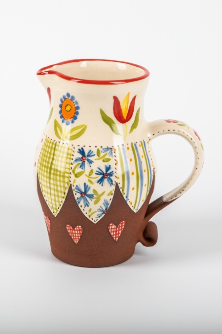 A photo of a decorative ceramic jug with two-tone/patchwork design and Tulip and folk art flowers on the side