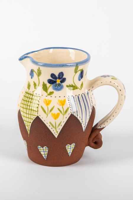 A photo of a decorative ceramic jug with two-tone/patchwork design and Blue pansy flowers on the side