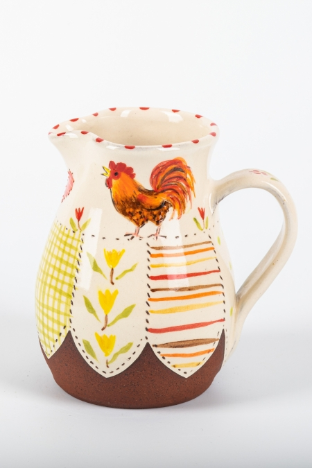 A photo of a decorative ceramic jug with two-tone/patchwork design with a chicken on the side