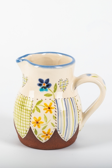 A photo of a decorative ceramic jug with two-tone/patchwork design with a pansy on the side