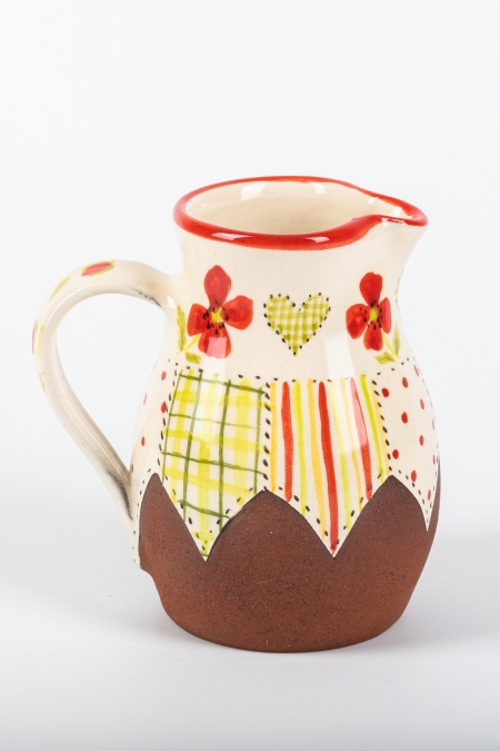 A photo of a decorative ceramic jug with two-tone/patchwork design with poppies on the side