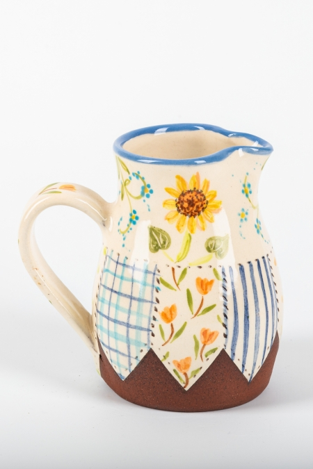 A photo of a decorative ceramic jug with two-tone/patchwork design with a sunflower on the side