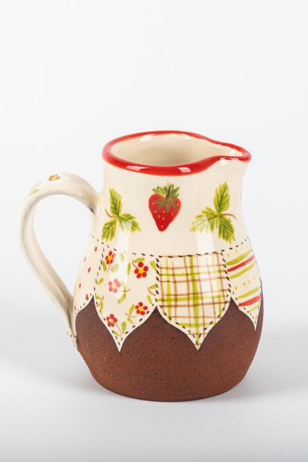 A photo of a decorative ceramic jug with two-tone/patchwork design with a strawberry on the side