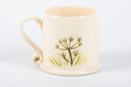 A photo of a small white mug with a wild flower on the side