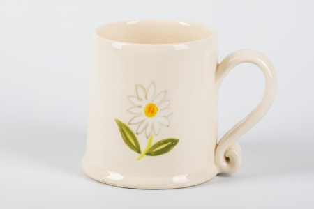 A photo of a small white mug with a daisy on the side