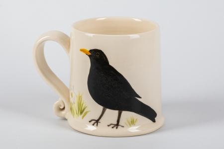 A photo of a small white mug with a blackbird Garden Bird on the side