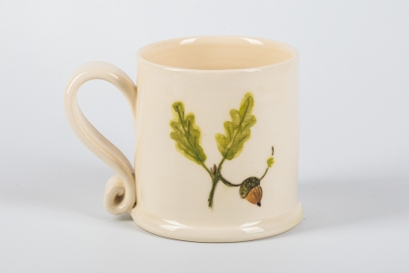 A photo of a small white mug with an acorn and oak leaves on the side