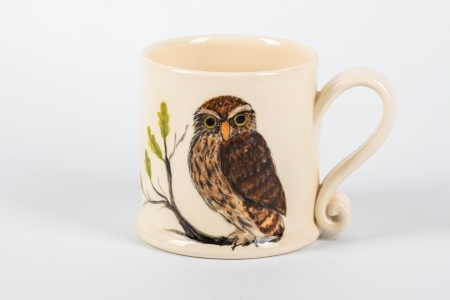 A photo of a small white mug with an Owl Garden Bird on the side