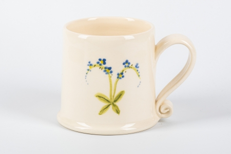 A photo of a small white mug with blue flowers on the side