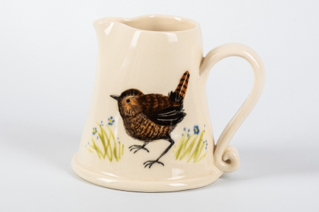 A photo of a small white jug with a wren garden bird on the side