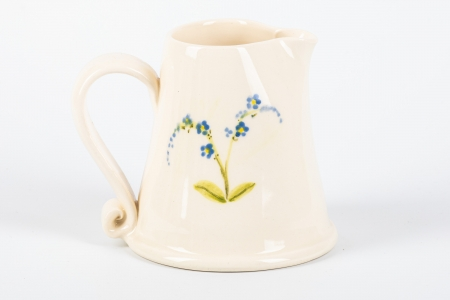 A photo of a small white jug with blue flowers on the side