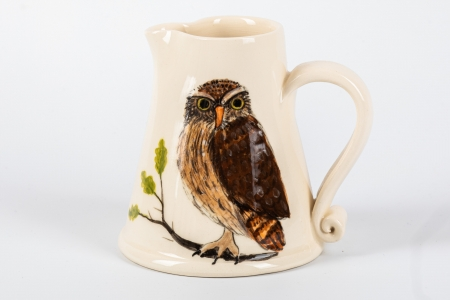 A photo of a small white jug with an Owl Garden Bird on the side