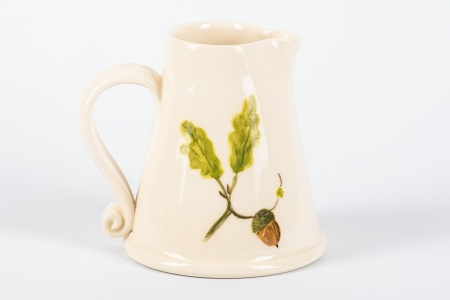 A photo of a small white jug with an acorn and oak leaves on the side