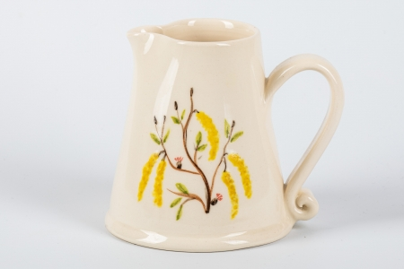 A photo of a small white jug with yellow flowers on the side