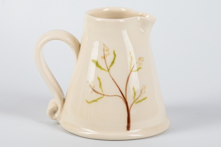 A photo of a small white jug with foliage on the side