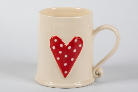 A photo of a white mug with a red heart with white dots heart on the side