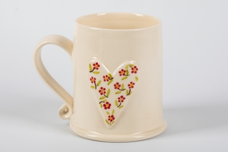 A photo of a white mug with a white heart with red dots on the side