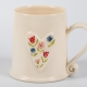 A photo of a white mug with a white heart with red, pink and blue flowers on the side