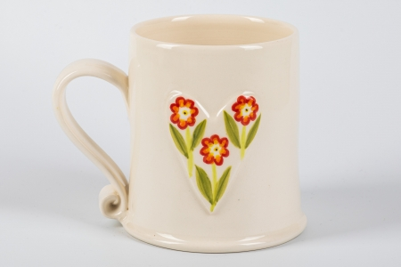 A photo of a white mug with a white heart with red flowers on the side