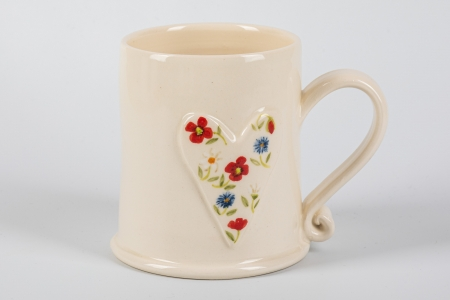 A photo of a white mug with a white heart with red and blue flowers on the side