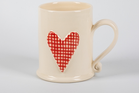 A photo of a white mug with a red gingham heart on the side