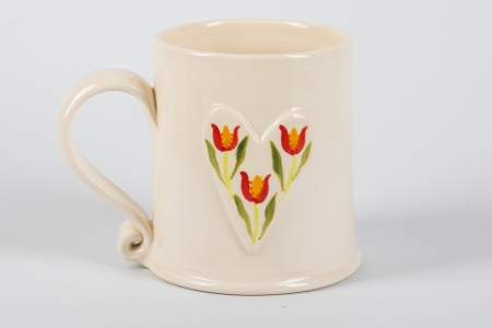 A photo of a white mug with a white heart with red tulips on the side