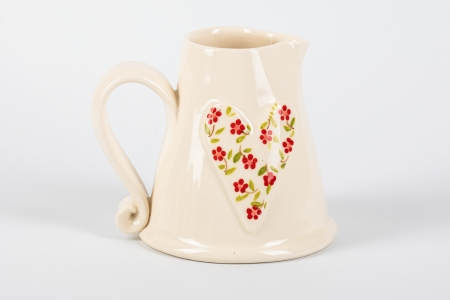 A photo of a white ceramic jug with a decorated heart on the side