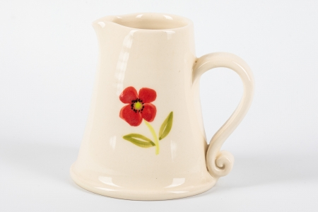 A photo of a small white jug with a red poppy on the side
