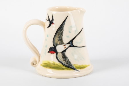 A photo of a small white jug with a swallow bird on the side